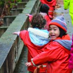 preschool students wearing rain gear walking across a bridge