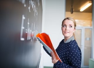 math teacher writing on chalkboard