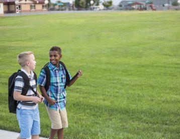 middle school boys walking, talking, wearing backpacks