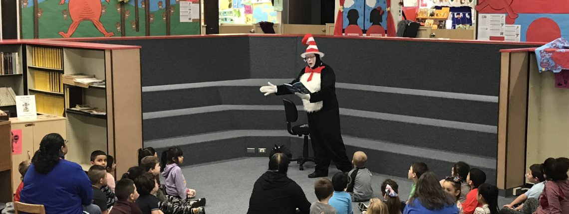 Teacher reading Cat in the Hat book to preschool students