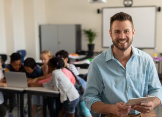 Teacher with a classroom of students behind him