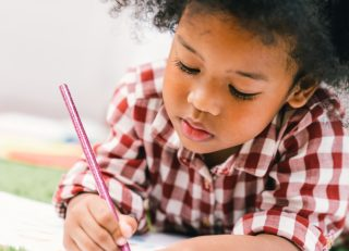 preschool child writing on a piece of paper