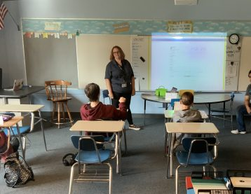 students sitting at desks, teachers at the front of the classroom