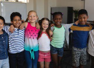 Happy school kids standing in classroom
