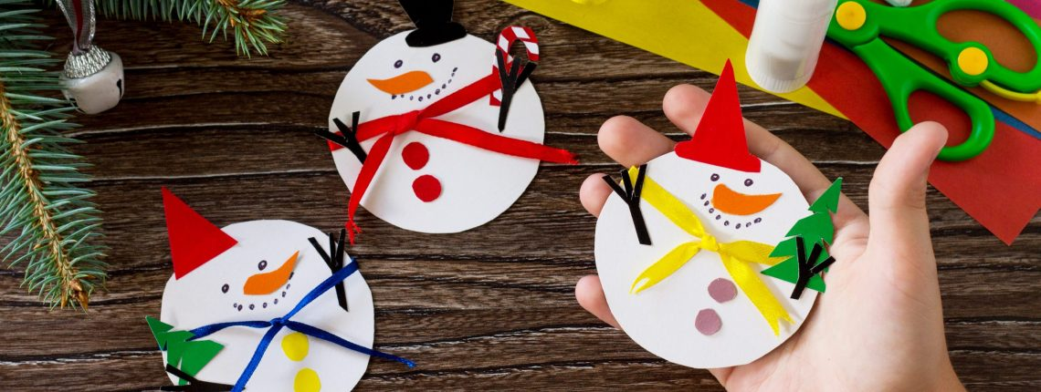 A child is holding Christmas snowman merry gift. Handmade. Project of children's creativity, handicrafts, crafts for kids.