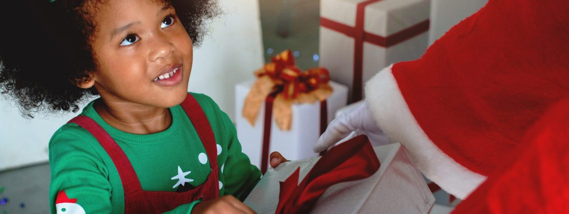 Happy little girl enjoying with Christmas gift, hands of Santa Claus give a child Christmas gift on Christmas time