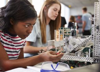 Two Female Students Building Machine In Science Robotics Or Engineering Class