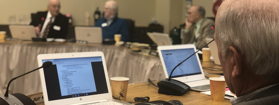 board members sitting around a table with laptops