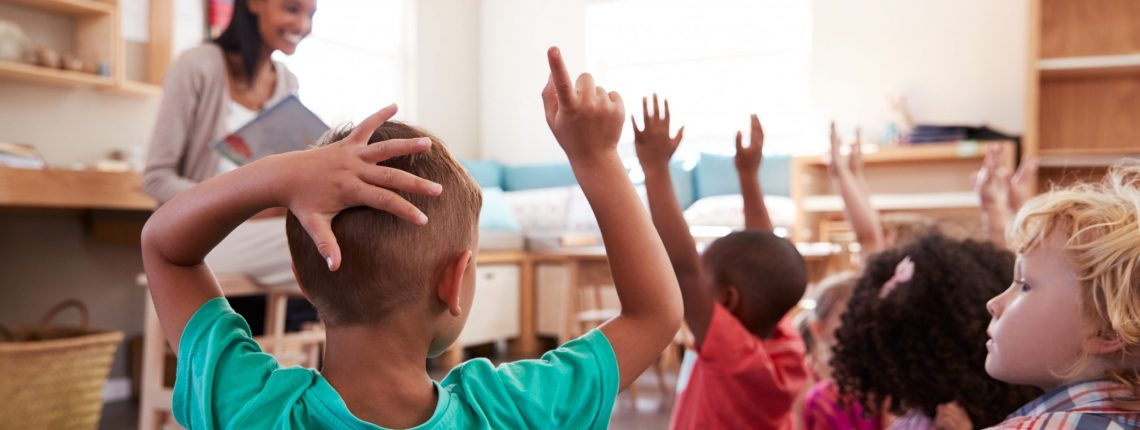 Pupils At School Raising Hands To Answer Question
