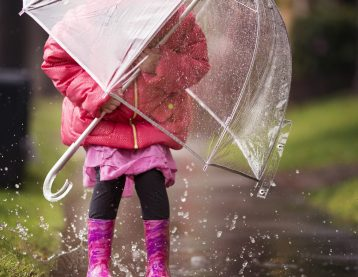 A young girl is playing in the rain.