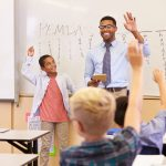Teacher and pupil with raised hands at front of school class
