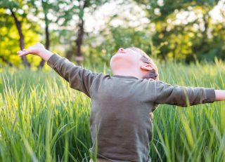 Child standing in a field looking at the sun