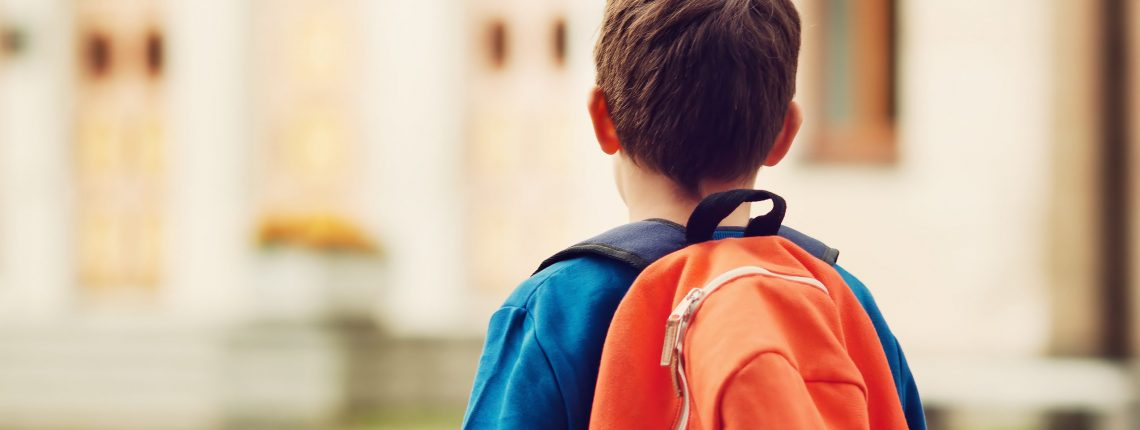 boy with backpack looking at a school