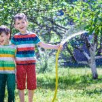 Boys playing with a garden hose