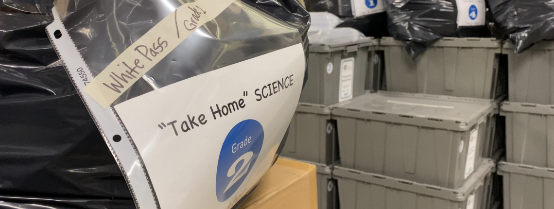 Take home science kits and gray claw boxes in a warehouse