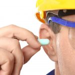 person wearing hard hat and safety goggles, holding an earplug