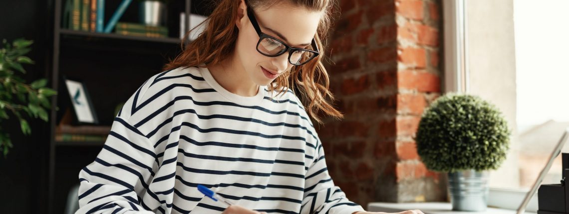 Happy millennial woman taking notes in notepad while working at laptop in comfortable loft office