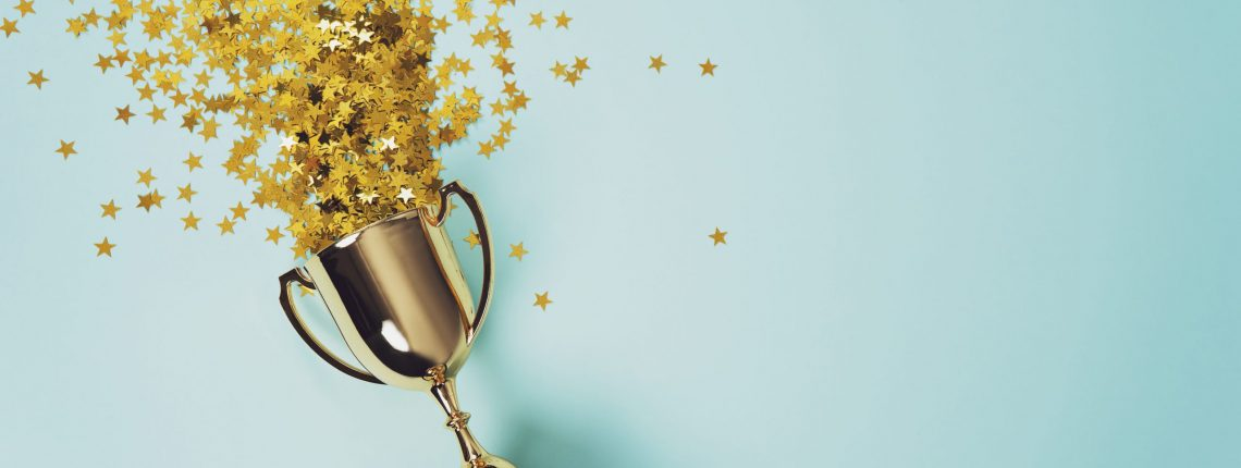 Gold trophy with star-shaped confetti on a light blue background.