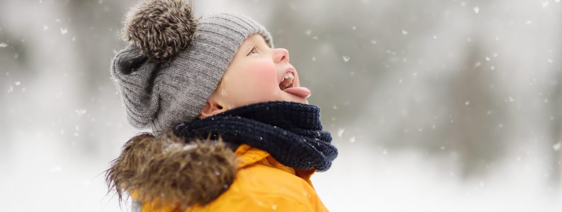 Child catching snowflakes on their tongue