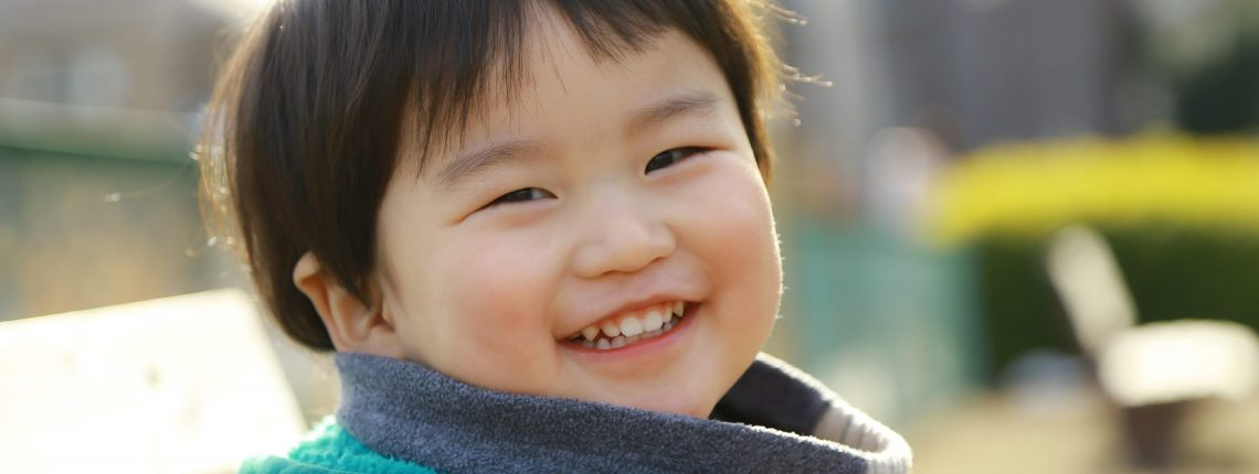 Child sitting in a park, smiling
