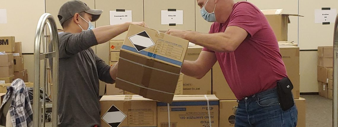 Two men wearing gloves and masks stack cardboard boxes with personal protection equipment.