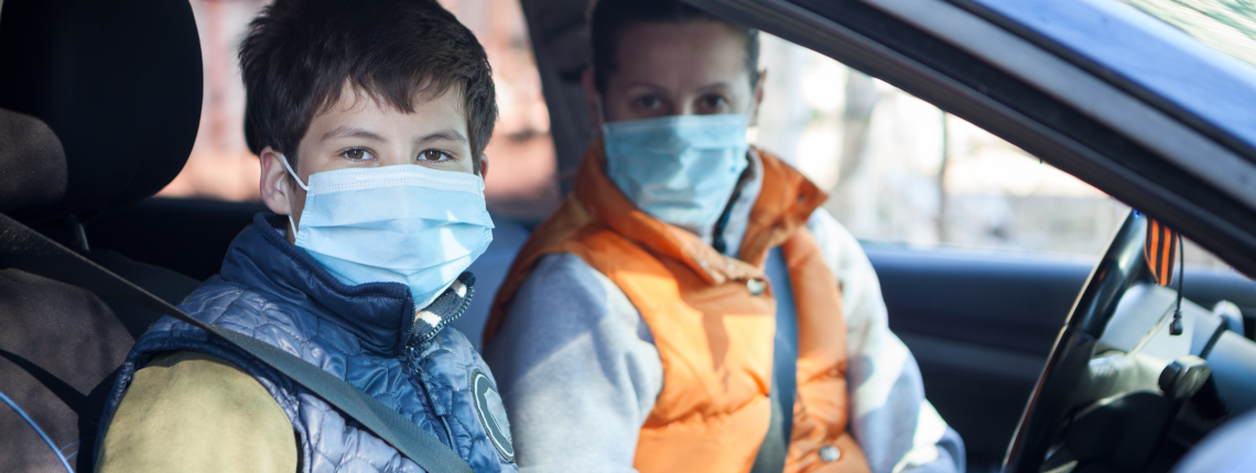 Preteen boy with his mother sitting inside car wearing medical masks, looking at camera