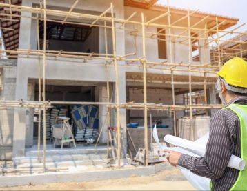 Professional engineer architect worker with protective helmet and blueprints paper at house building construction site
