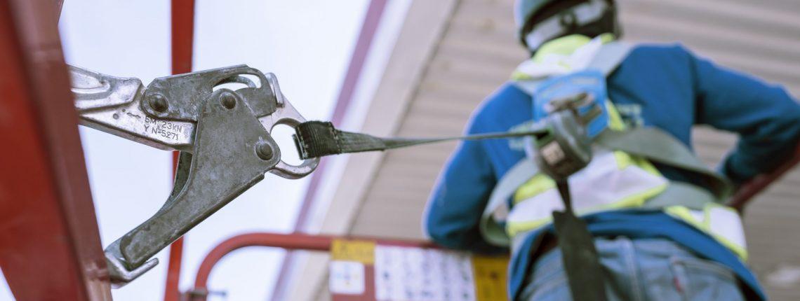 Worker on a Scissor Lift Platform working at site focus on full harness safety belt