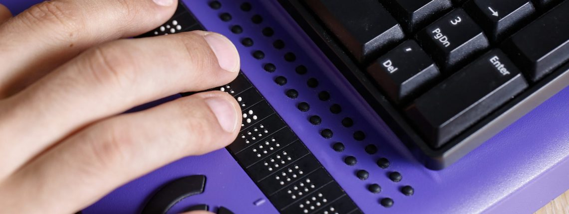 Person using refreshable braille display