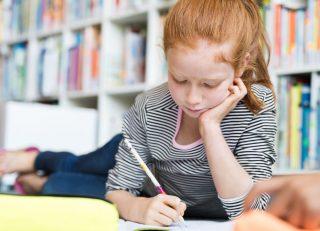 Girl lying on floor doing homework