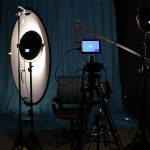 Rainier Production Studio. Room with black walls, a blue photography studio backdrop and cameras, a microphone, and studio lights.