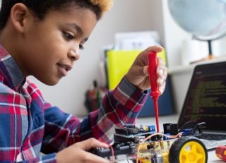 Elementary student builds robotic car in classroom