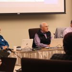 Three men sitting in a board of directors meeting.
