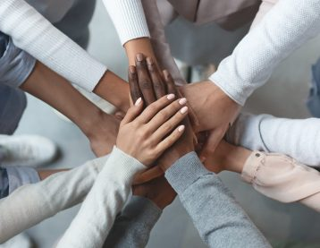 A diverse group of coworkers puts their hands together